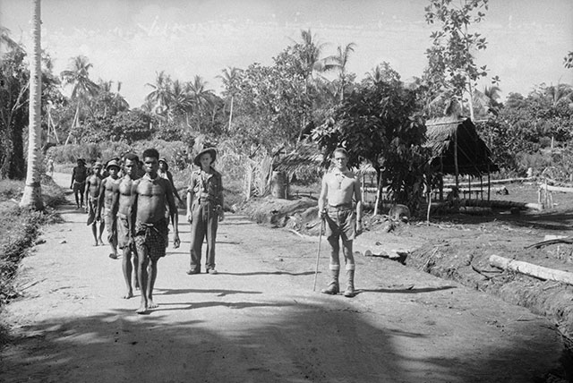 Papuan carriers passing through a village, 1942